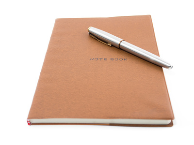 Brown notebook with pen isolated on white